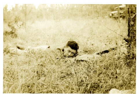 Soldier laying in a field (ddr-densho-22-227)