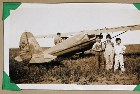 Three boys stand in front a plane (ddr-densho-404-358)
