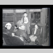 Adult male and three children from Terminal Island sit on benches in a train car (ddr-csujad-54-4)
