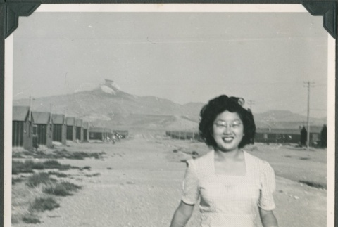 Woman walking in Heart Mountain concentration camp (ddr-densho-321-116)