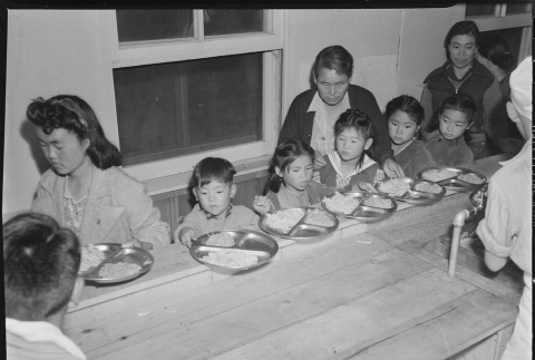 Japanese Americans eating in a mess hall (ddr-densho-37-482)