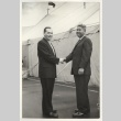 Two men shaking hands in front of the convention tent (ddr-jamsj-1-513)
