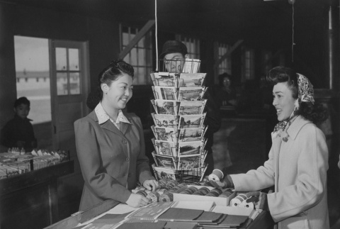 Young Nisei girl purchasing Christmas wrappings in cooperative notion store at Granada incarceration camp (ddr-csujad-14-40)