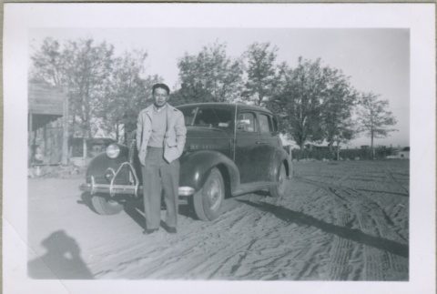 A man standing in front of a car (ddr-densho-300-37)