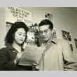 Military recruit filling out Selective Service paperwork with a woman (ddr-densho-22-493)