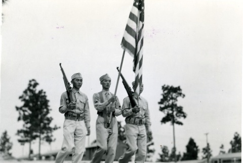 Three soldiers marching with a flag and rifles (ddr-densho-22-487)