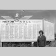 Female soldier standing in front of the Honor Roll at Minidoka (ddr-fom-1-397)