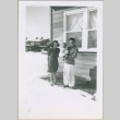 A family outside of a housing project apartment (ddr-densho-300-60)