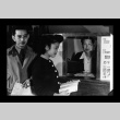 Henry Tsuno and Helen Akahoshi in the cashier office, Amache Co-op (ddr-csujad-55-1551)