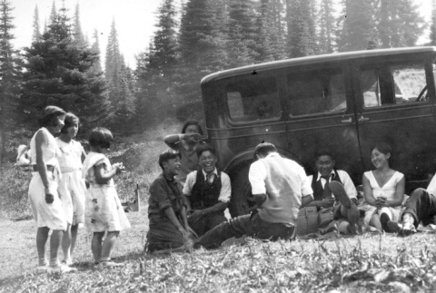 Nisei youth relaxing in front of car (ddr-densho-134-17)