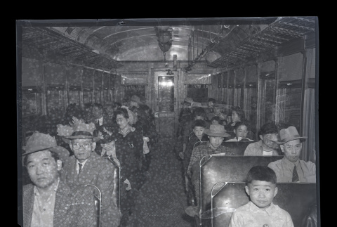 Large group of Japanese American people from Terminal Island fill a vehicle during
