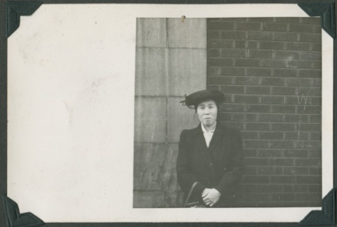Woman standing by brick a building (ddr-densho-321-124)