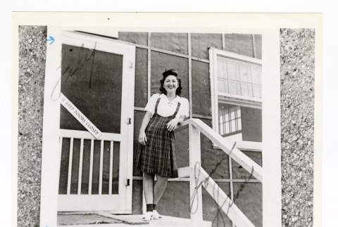 Sumi Seki wears a white shirt and plaid skirt while standing in front of barracks (ddr-csujad-52-45)