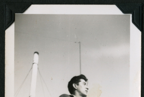 A man in a jacket stands holding a cigarette (ddr-densho-390-90)