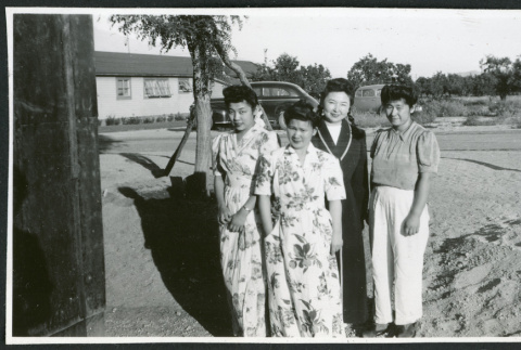 Photograph of four women posing next to a building with two cars in the background at Manzanar (ddr-csujad-47-197)