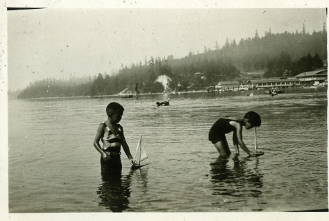 Children playing in water with sailboats (ddr-densho-182-85)