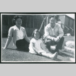 Photograph of Dr. and Mrs. Jiro Muramoto with daughter posing in front of the Manzanar hospital, with a nurse standing in the entrance (ddr-csujad-47-220)
