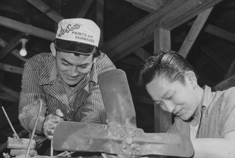 George Baba and Tokiji Umeda overhauling a truck loader in motor pool repair section at Rohwer incarceration camp (ddr-csujad-14-24)