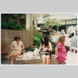 Tomi Iino and young woman eating food outside shopping center. (ddr-densho-368-315)