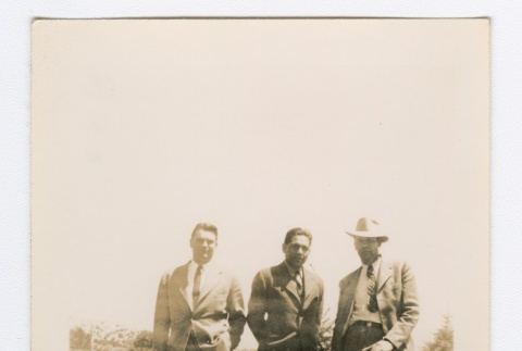 Three men in suits standing behind a low wall (ddr-densho-223-39)