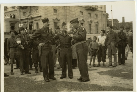 Soldiers smoking with civilians looking on (ddr-densho-201-125)