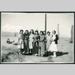 Photograph of eight women standing outside next to a barracks with the Sierra Nevada in the background (ddr-csujad-47-186)