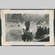 Young man crouching by charred logs (ddr-densho-321-227)