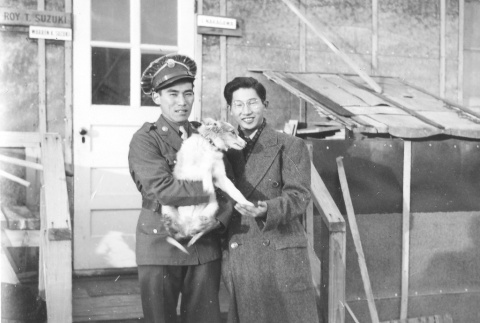 A soldier and a man in civilian clothes holding a dog in front of  barracks at Minidoka concentration camp, Idaho (ddr-densho-243-1)