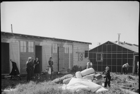 Bedding and clothing in front of barracks (ddr-densho-151-456)