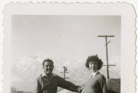 Man and woman standing in front of a car (ddr-manz-8-7)