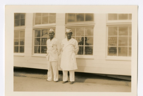 Two men with white caps and smocks in front of a row of windows (ddr-densho-223-36)