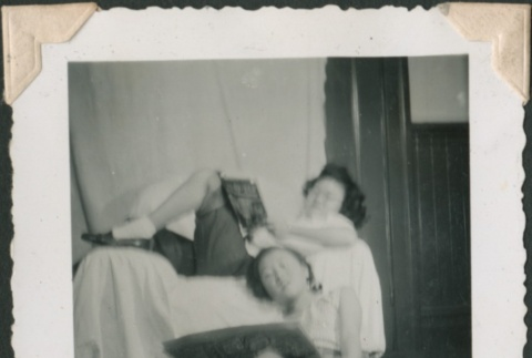 Two young women lounge with books (ddr-densho-321-235)
