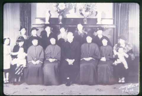 Priest, Nuns, women and children in front of fireplace (ddr-densho-330-16)