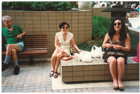 Tomi Iino and young woman eating food outside shopping center. (ddr-densho-368-314)