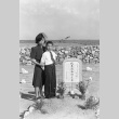 Mother and son standing next to a grave (ddr-fom-1-158)