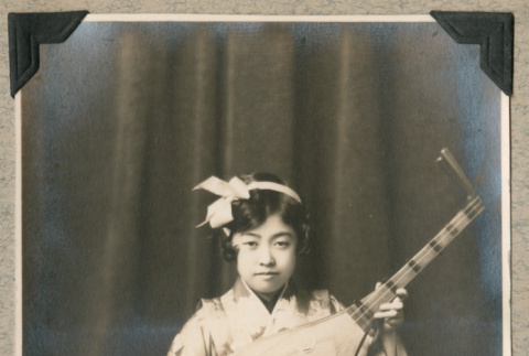 Portrait of girl dressed in kimono with instrument (ddr-densho-383-236)
