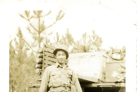 Soldier standing next to a truck with gear (ddr-densho-22-201)