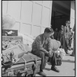 Japanese American waiting with baggage (ddr-densho-151-103)