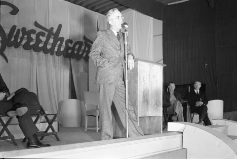 Harry L. Stafford speaking on a stage before a Sweetheart dance (ddr-fom-1-431)