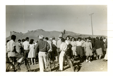 People gathering around a vehicle covered in baggage (ddr-csujad-26-91)