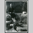 Photograph of a man in a robe sitting on a rock wall in front of the Manzanar hospital (ddr-csujad-47-245)