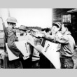 Nisei helping to post exclusion orders (ddr-densho-34-46)