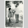 Photograph of an artist painting at an easel while a young girl watches (ddr-csujad-47-72)