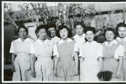 Photograph of eight hospital staff aides standing in front of the Manzanar hospital (ddr-csujad-47-196)