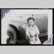 Young boy grins in front of a car (ddr-densho-404-33)