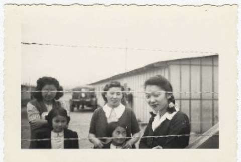 Women and girls behind barbed wire at Camp Harmony (ddr-densho-383-464)