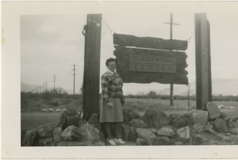 Woman standing in front of camp entrance sign (ddr-manz-7-2)