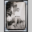 Young man stands in a yard (ddr-densho-404-205)
