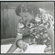 Photograph of Irene Gavigan leaning over an infant at Manzanar (ddr-csujad-47-227)
