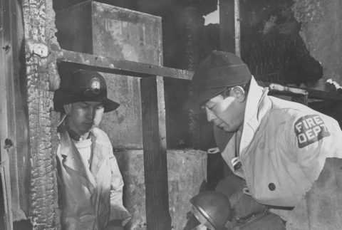 Two members of the Fire Prevention Squad inspecting remains of dormitory fire at Heart Mountain incarceration camp (ddr-csujad-14-54)